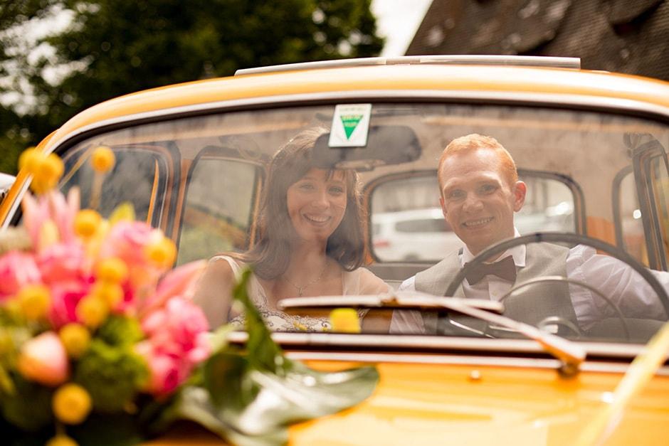 Brautpaar im Brautauto für Foto-Shooting