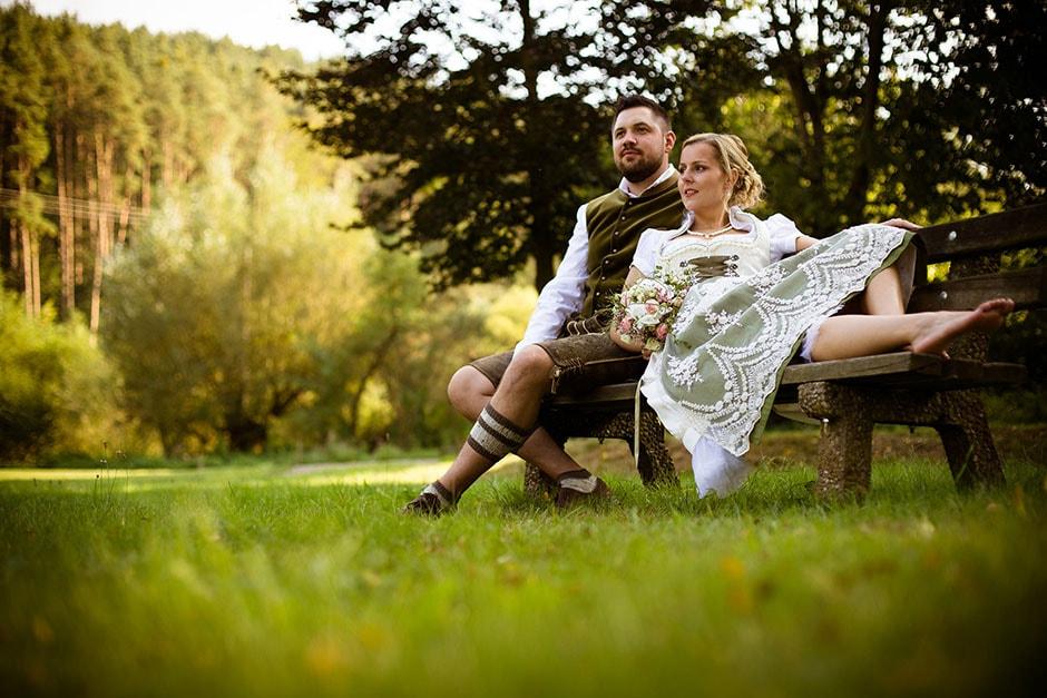 Brautpaar im Dirndl auf Bank in der Natur