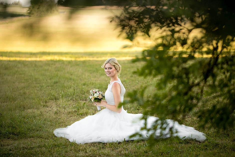 Braut mit Brautstrauß auf Wiese