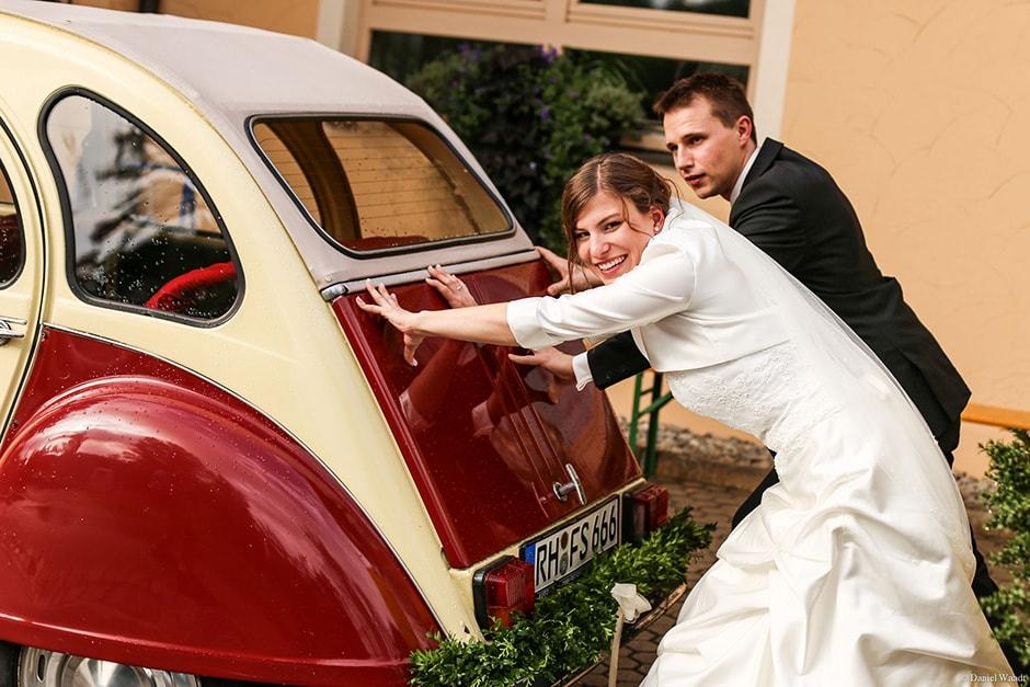 Brautpaar schiebt Brautauto
