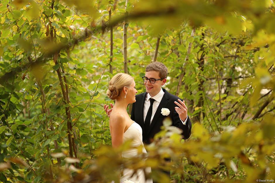Brautpaar versteckt sich in den Sträuchern
